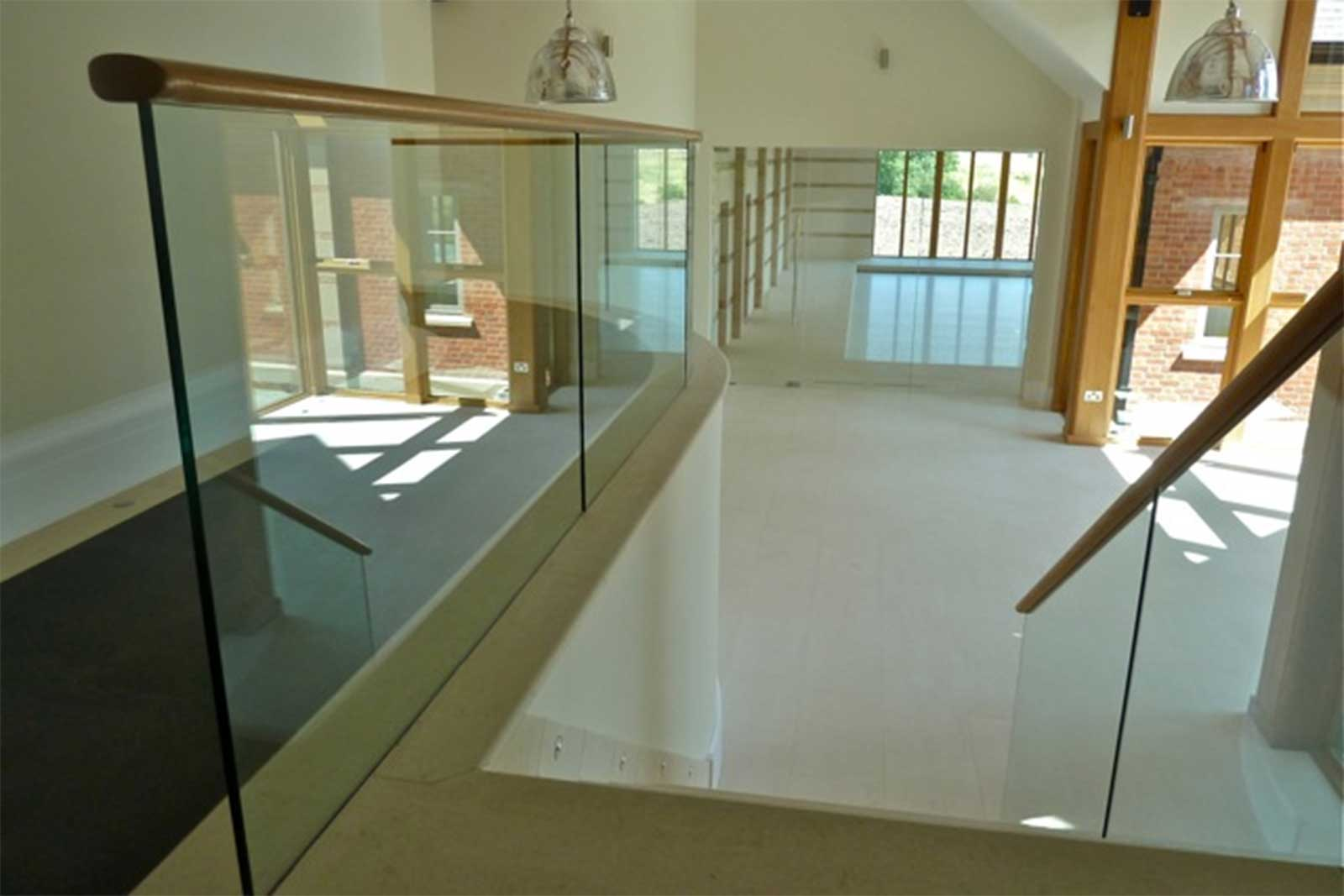 Frameless glass balustrade with bespoke wooden handrail