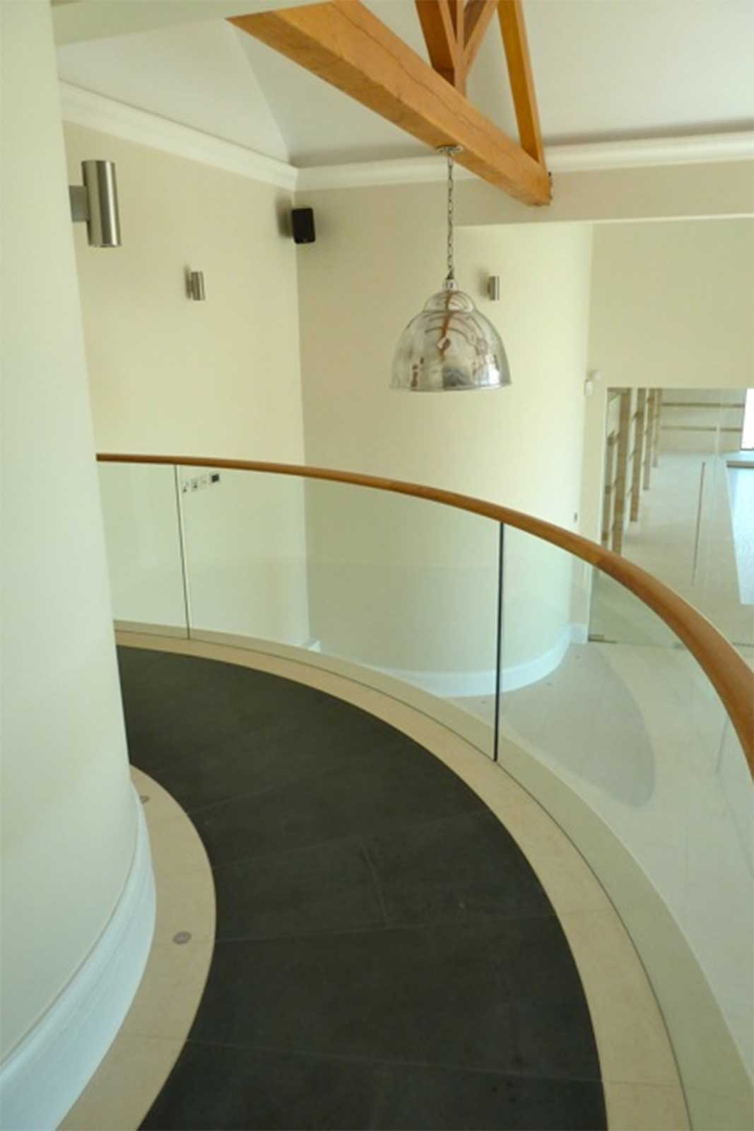 Curved Glass Balustrade with bespoke wooden handrail