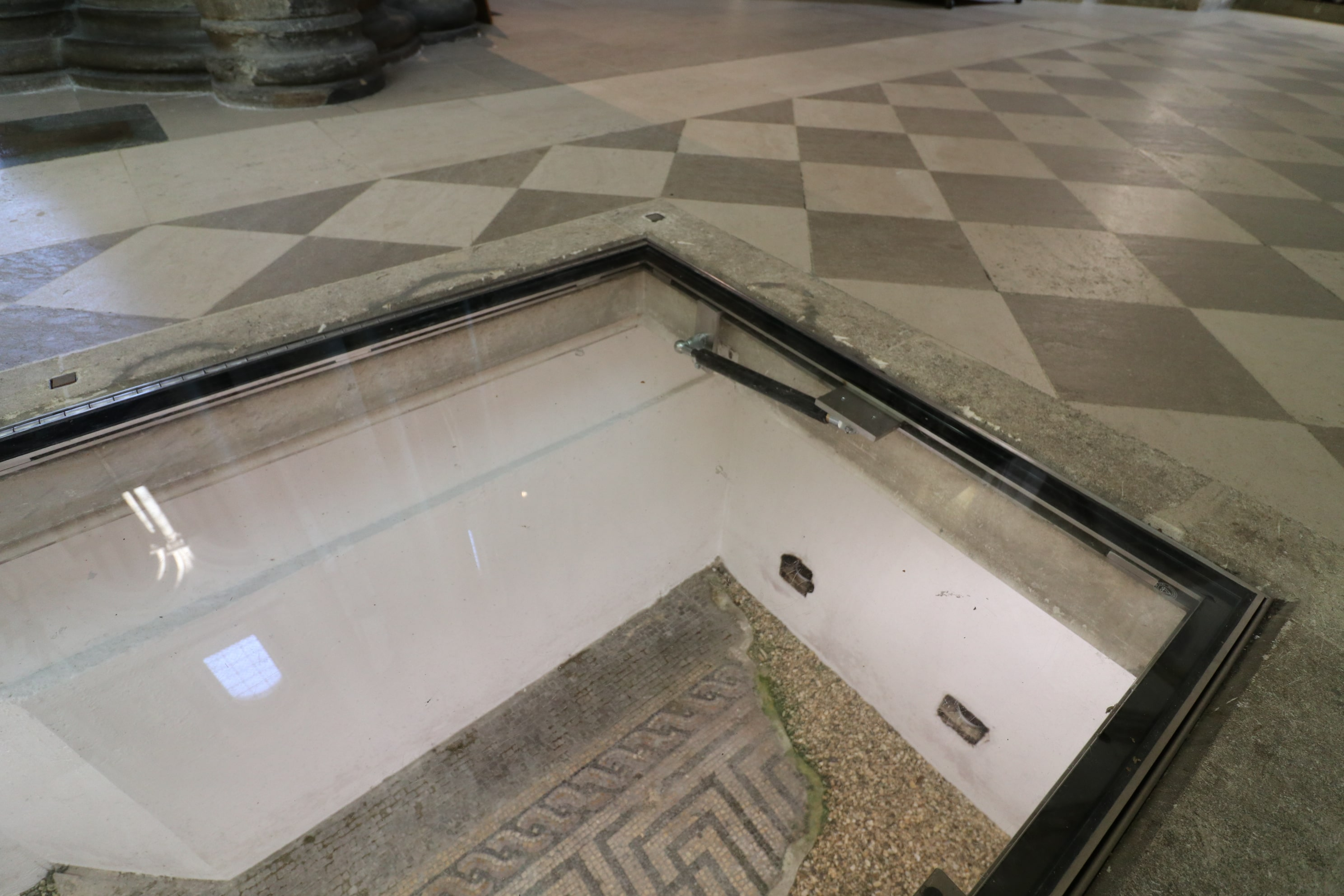 Walk on glass floor panel with lifting mechanism over Roman mosaic
