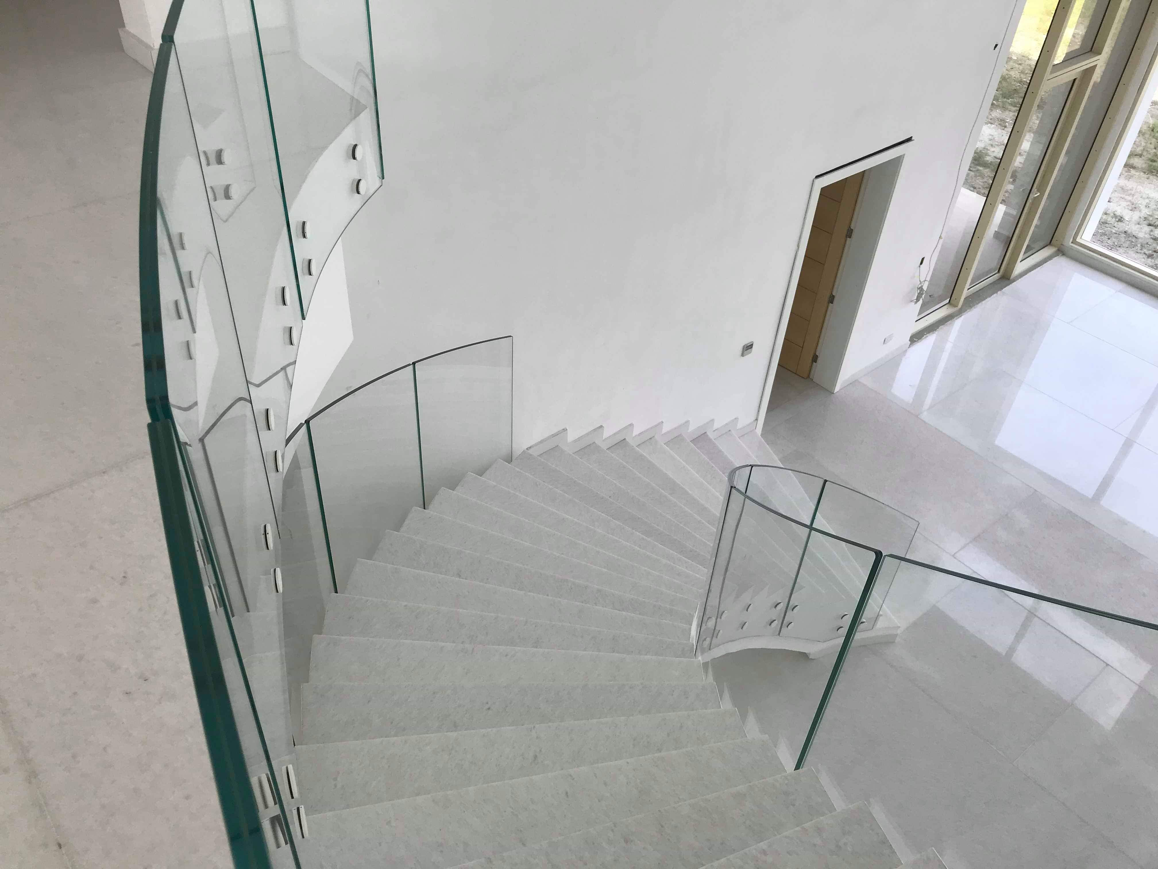 Bolted curved glass balustrade to marble staircase