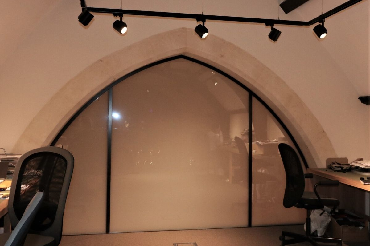 Arched glass screen creating office at St Dionis Church in switchable glass obscured