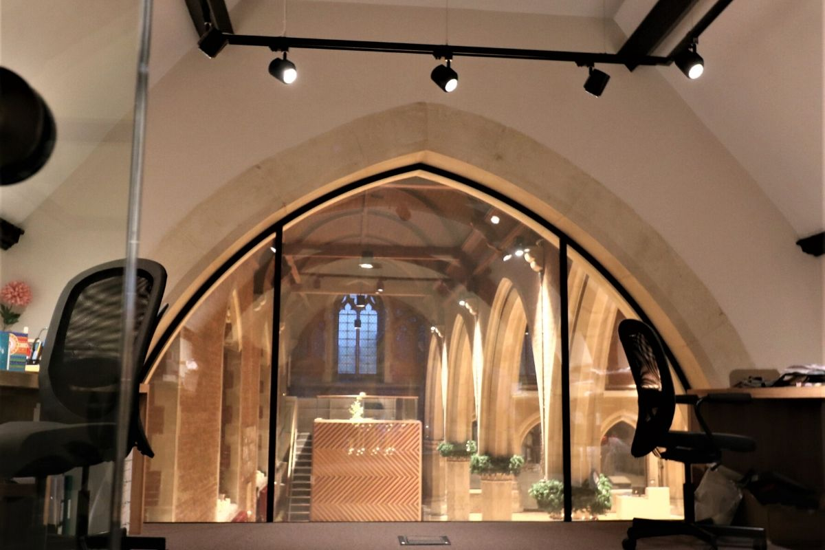 Arched glass screen creating office at St Dionis Church in switchable glass