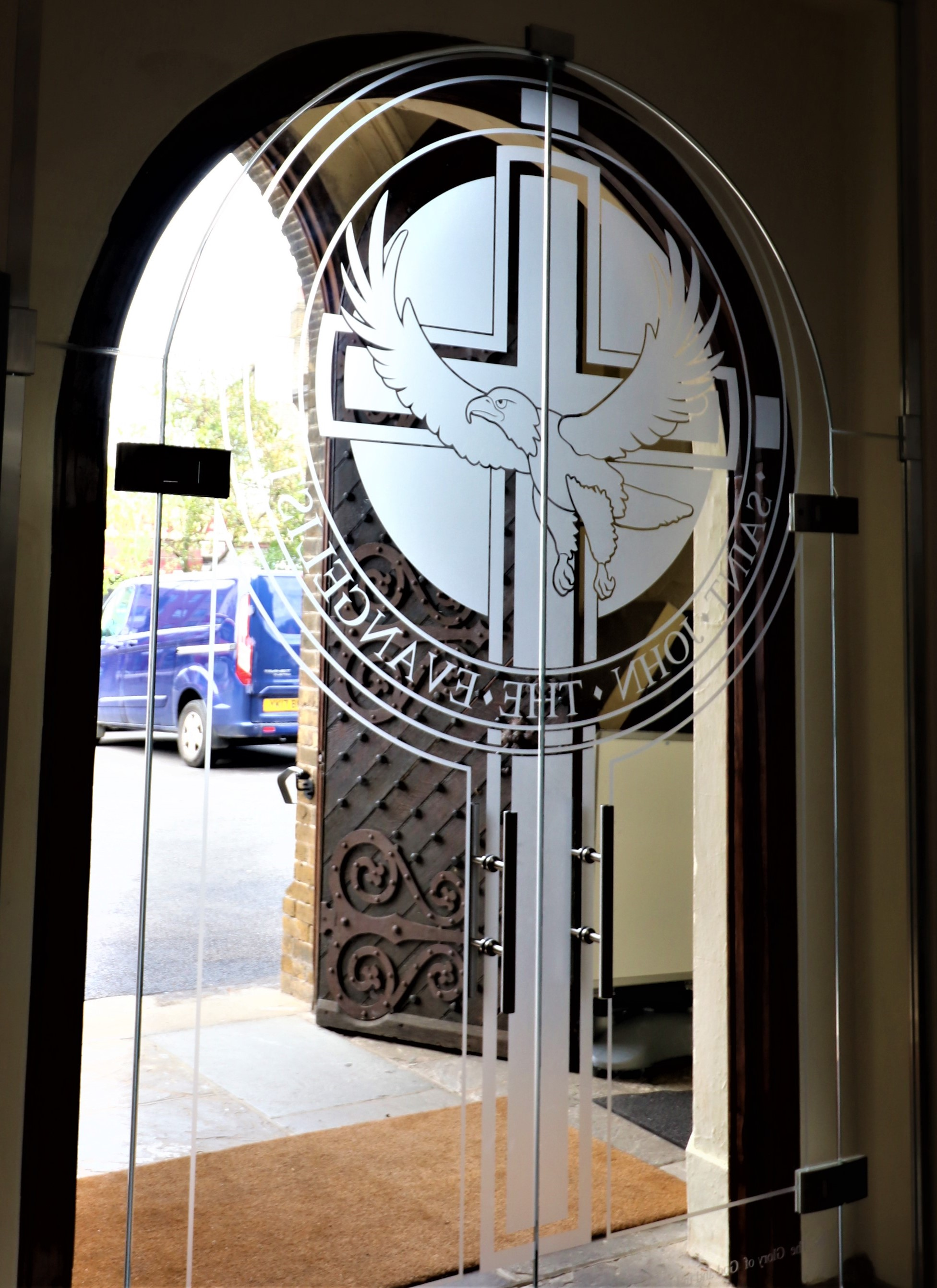 Eagle manifestation to frameless glass door, st Johns Church
