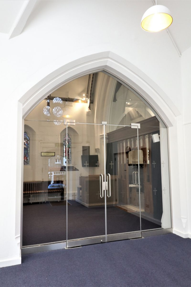 Double framless glassd doors with manifestations fitted to arched screen, St Mary Church